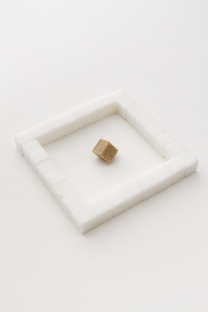 white sugar cube, place in a square, with an brown sugar square at an angle photo