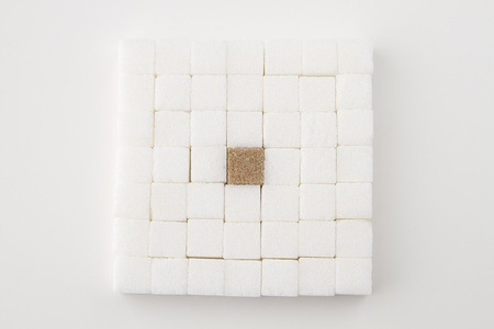 white sugar cube, place in a square, with an brown sugar square in the middle photo