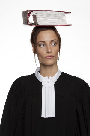 Women dress as a canadian attorney, balancing a red book of law on it on her head photo