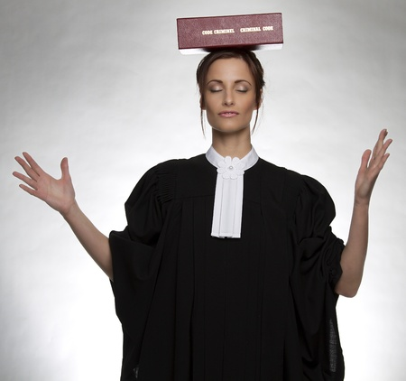 Women dress as a canadian attorney, with her eyes close, balancing a red book of criminal law with bilingual text on it on her head photo