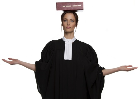 Women dress as a canadian attorney, balancing a red book of criminal law with bilingual text on it on her head photo