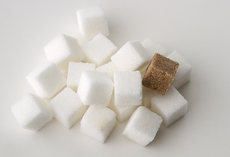 stack of white sugar cube with one brown sugar cube photo