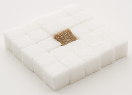 white sugar cube with one brown sugar cube place in a square shape photo