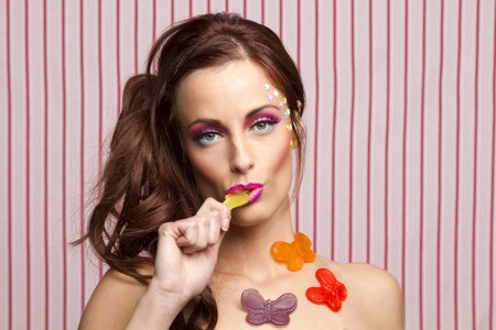 Young woman with colorful makeup and star candy glued to her face and gummy butterfly glued to her body, sucking on the wing of a yellow butterfly Stock Photo - 13443550