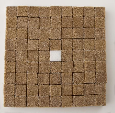 Brown sugar square in a square with one white one in the middle photo