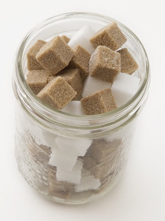 Brown and white sugar cube in a glass jar photo