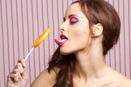 Young woman with colorful makeup and star candy glued to her face, licking an orange lollipop photo