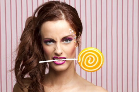 Young woman with colorful makeup and star candy glued to her face, holding an orange lollipop by the stick between her teeth photo