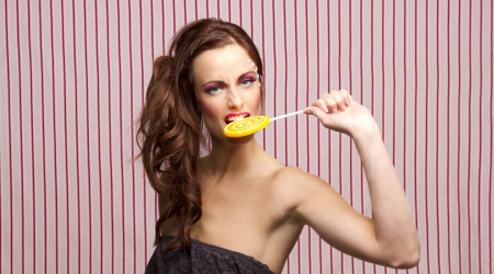 Young woman with colorful makeup and star candy glued to her face, bitting an orange lollipop  photo