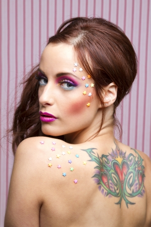Young woman with colorful makeup and star candy glued to her face and her back photo