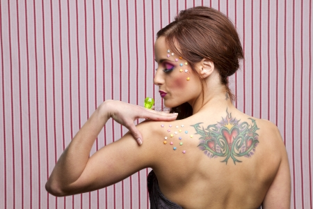 Young woman with colorful makeup and star candy glued to her face and body, blowing on a lollipop ring photo