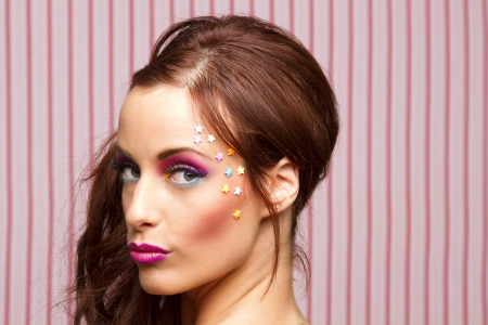 Young woman with colorful makeup and star candy glued to her face  Stock Photo - 14121383