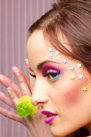 Young woman with colorful makeup and star candy glued to her face, showing a lollipop ring photo