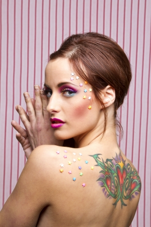 Young woman with colorful makeup and star candy glued to her face and back photo