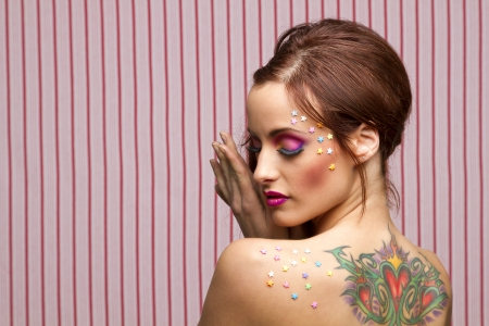 Young woman with colorful makeup and star candy glued to her face and back with her eyes close photo