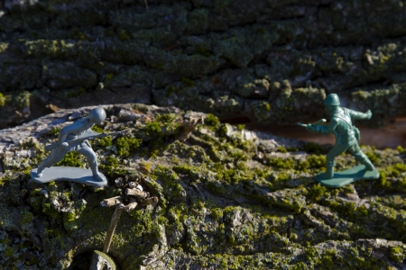 gray and green toy soldier fighting on top of tree bark photo