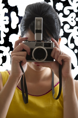 young woman in front of a black and white textured background with 60s inspired style, holding a SLR 35mm film camera photo