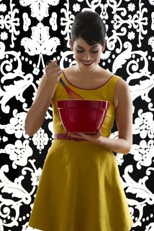 young woman in front of a black and white textured background with 60's inspired style, holding a red whisk in a red bowl