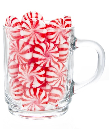 hard red and white candy mints in a transparent cup