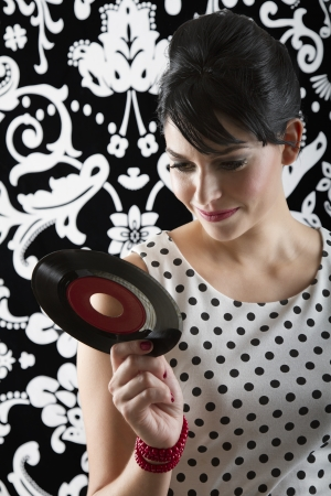 young woman reading the label of a small record Stock Photo - 17638879