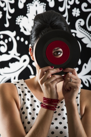 young woman looking through the hole of a small dusty record with a red label photo
