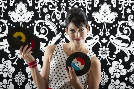 young woman is stylist 60s inspired clothing, showing off three vinyl records photo