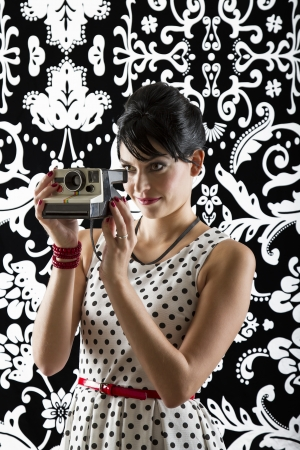 young woman is stylist 60's inspired clothing, holding an instant camera and preparing to take a photo photo