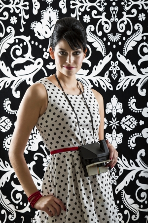 young woman is stylist 60s inspired clothing, holding an instant camera photo