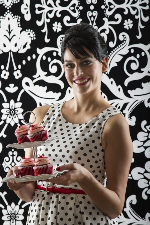 gumpaste: young woman is stylist 60s inspired clothing, serving a plate of velvet cupcake with a smile