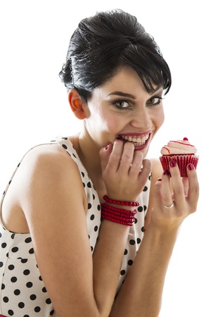 young woman bitting her finger and holding a velvet cupcake photo