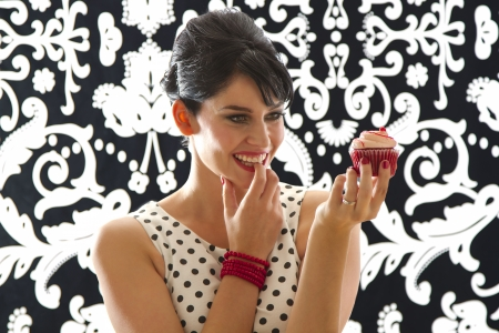 young woman is stylist 60's inspired clothing, holding up a velvet cupcake with tempeted look photo
