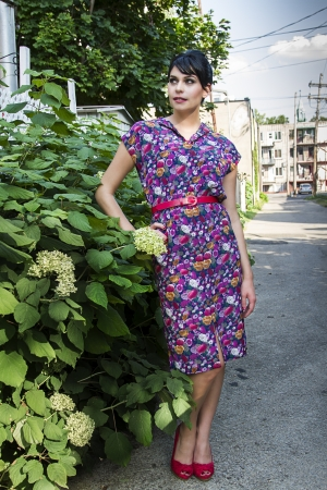 Young fashionable woman wearing a multi colored flower pattern dress near a flower bush in an urban alley photo