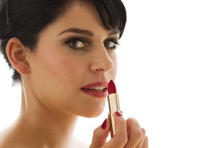 赤い口紅を適用する若い女性