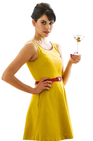Young woman wearing a bring yellow dress having a sip of a three olive martini photo