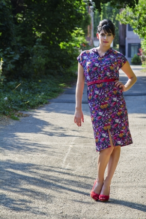 Young fashionable woman wearing a multi colored flower pattern dress standing in an urban alley photo