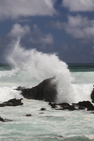 volcanic rock formation being pounded by wave