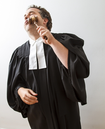 Man in canadian lawyer toga slamming a hammer into his face
