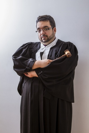 Man in canadian lawyer toga holding a hammer against a white background Stock Photo