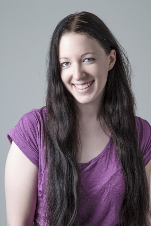 Young woman in purple shirt with a great big smile against a gray background photo