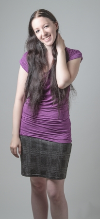 cute young woman in purple shirt and gray plaid skirt against a gray background photo