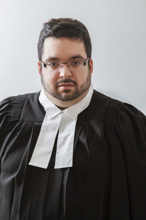 Overweight man in canadian lawyer toga against a white background photo