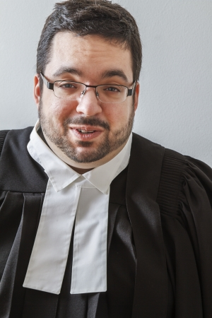 Overweight man in canadian lawyer toga, with happy expression, against a white background photo