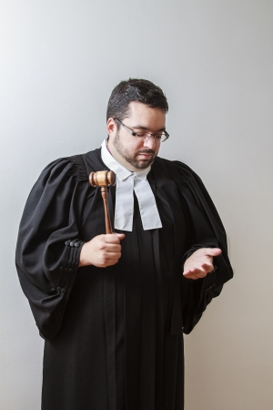 Overweight man in canadian lawyer toga, pounding a gavel in his hand photo