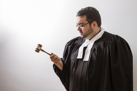 Overweight man in canadian lawyer toga, looking intensely at a gavel in his hand photo