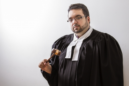 Overweight man in canadian lawyer toga, with a gavel in his hand photo