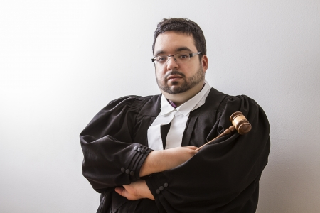 Overweight man in canadian lawyer toga, with arms cross, holding a gavel in his hand photo