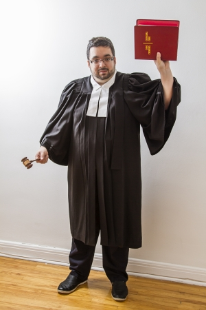 Overweight man in canadian lawyer toga, holding a gavel in his hand and a red bilingual criminal law book in the other photo