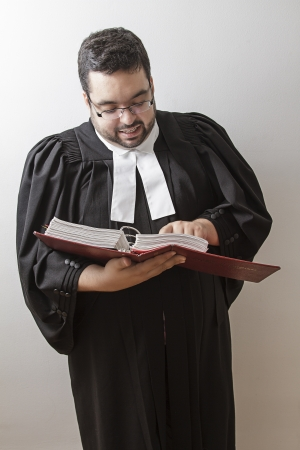 Overweight man in canadian lawyer toga, holding a red bilingual criminal law book and reading in it photo