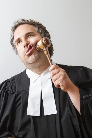 Man in Canadese laywer gewaad slaande een hamer op zijn gezicht Stockfoto