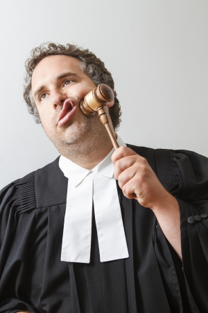 Man in canadian laywer robe slamming a gavel on his face Stock Photo
